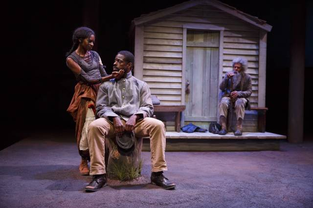 """Jenny Jules, Sterling K. Brown, and Peter Jay Fernandez in """"Father Comes Home from the Wars (Parts 1, 2 & 3)"""" by Suzan-Lori Parks and directed by Jo Bonney, running at The Public Theater. Photo credit: Joan Marcus."""