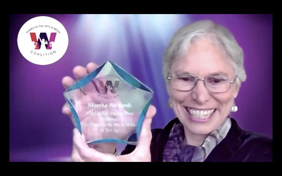 screenshot of Martha Richards holding up the award