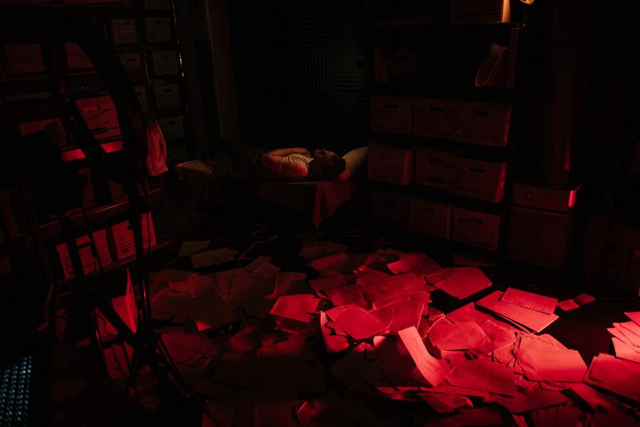 Man sleeping with scattered papers on the floor